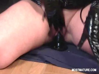 aged tramp in latex riding fake penis and finger