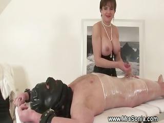 Topless domina jerks off her bound slave