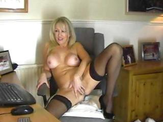 Blonde milf in black stockings masturbates on a
