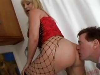 aged blonde in fishnet nylons and boots receives