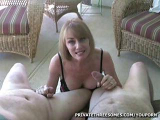 Busty blonde milf is giving two guys and handjob